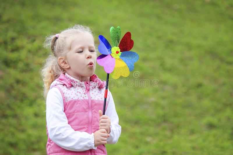 Little blonde girl holding multicolored pinwheel in her ha stock images