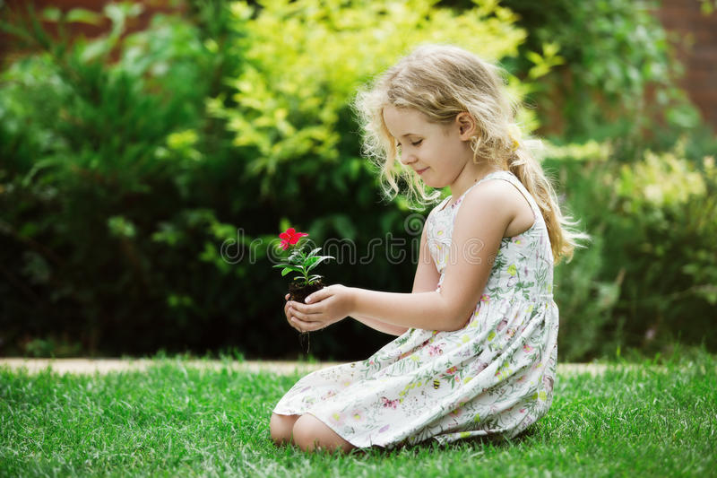 Little blonde girl holding young flower plant in hands on green background.  stock photos