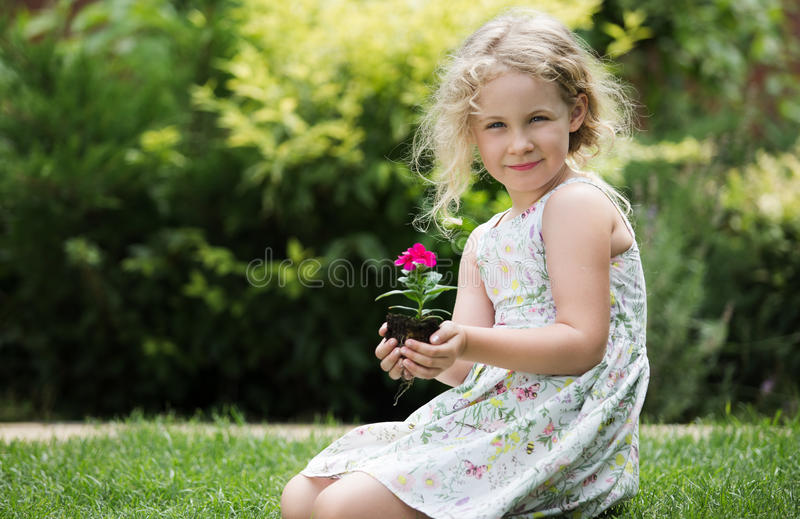 Little blonde girl holding young flower plant in hands on green background.  stock photography