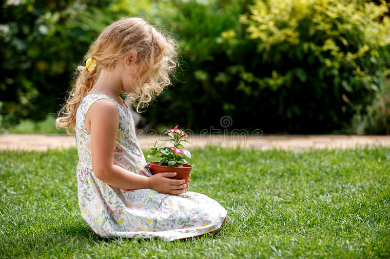 Little blonde girl holding young flower plant in hands on green background. stock images