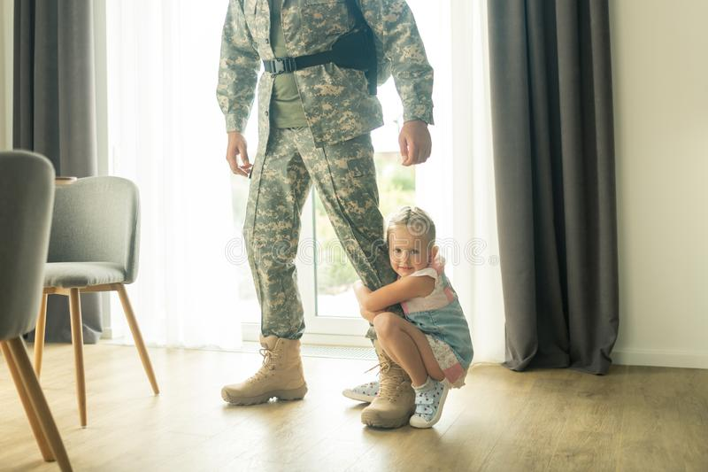 Little blonde girl hugging her father leg while he leaving house. Hugging father leg. Little blonde girl hugging her father leg while he leaving house for stock image
