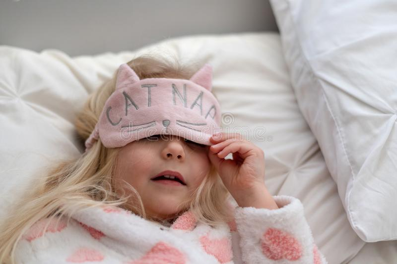 Little blonde girl laying on bed for a nap royalty free stock photography