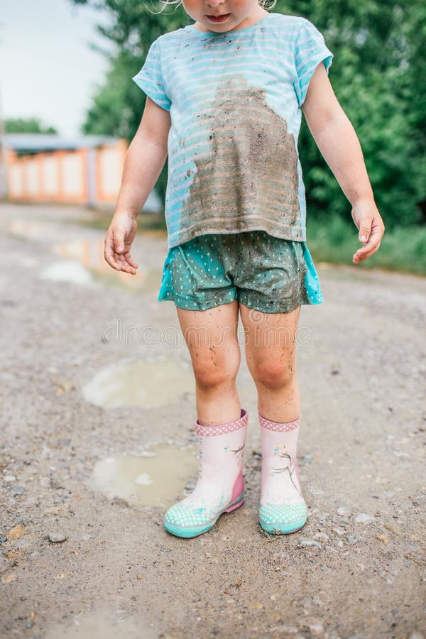 Little blonde girl looks at her dirty clothes after fall into a puddle stock image