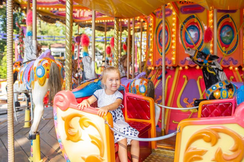 Little blonde girl on old french carousel in a holiday park. Charming cute little girl in a dress is smiling and enjoy royalty free stock images