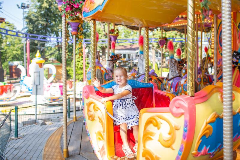 Little blonde girl on old french carousel in a holiday park. Charming cute little girl in a dress is smiling and enjoy royalty free stock photo