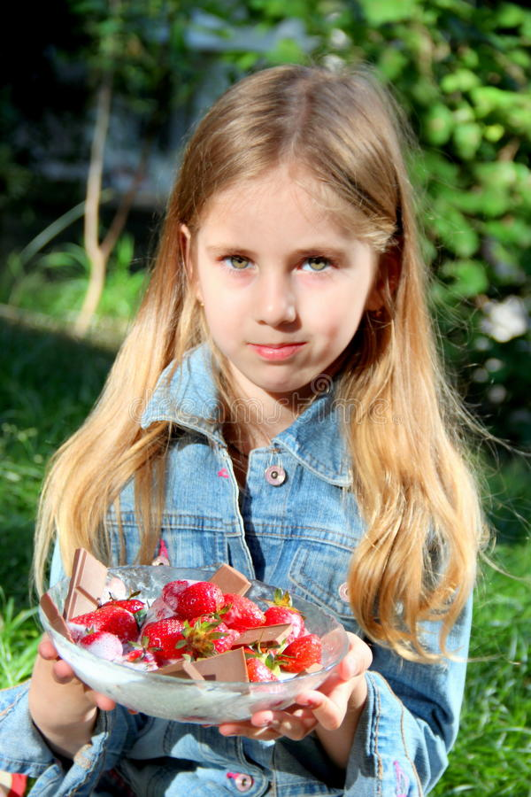 Little blonde girl with a plate of fresh strawberries in summertime royalty free stock photography