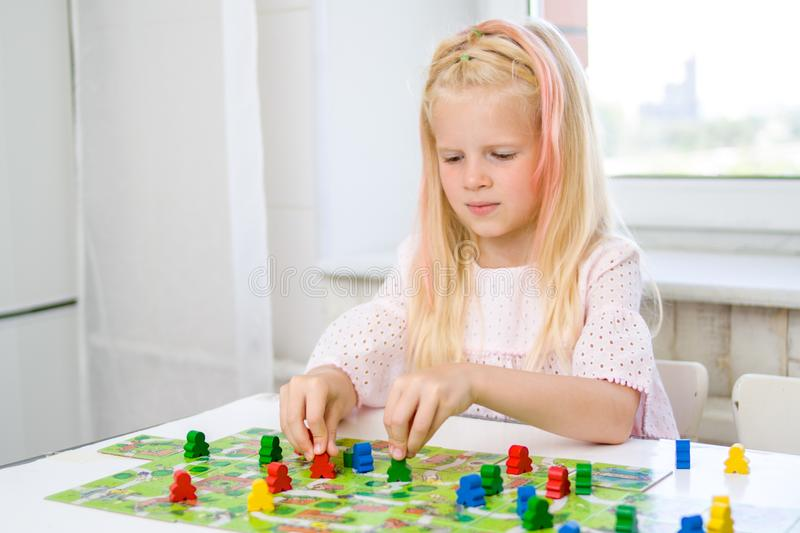 little blonde girl is playing - hold people figures in hand. yellow, blue, green wood chips in children play - Board game and kids stock photo