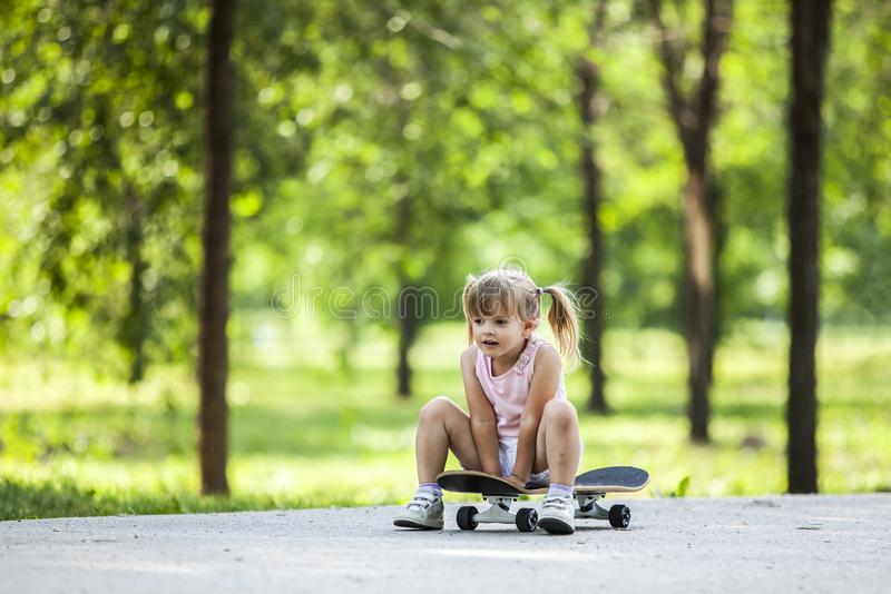 Little blonde girl playing with skateboard in forest park. During summer sunny day stock images
