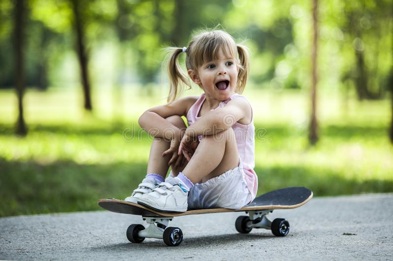 Little blonde girl playing with skateboard in forest park. During summer sunny day royalty free stock photography