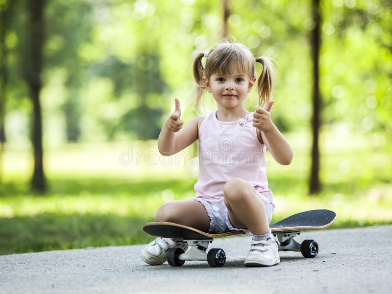 Little blonde girl playing with skateboard in forest park. Ttle blonde girl playing with skateboard in forest park during summer sunny day royalty free stock images