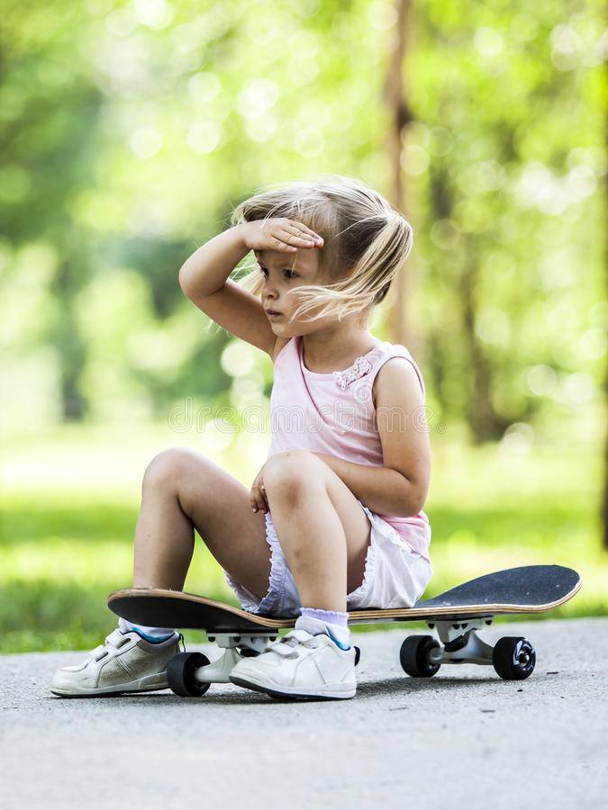 Little blonde girl playing with skateboard in forest park. Ttle blonde girl playing with skateboard in forest park during summer sunny day stock photography