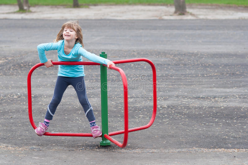 Little blonde girl playing on small merry go round stock photos