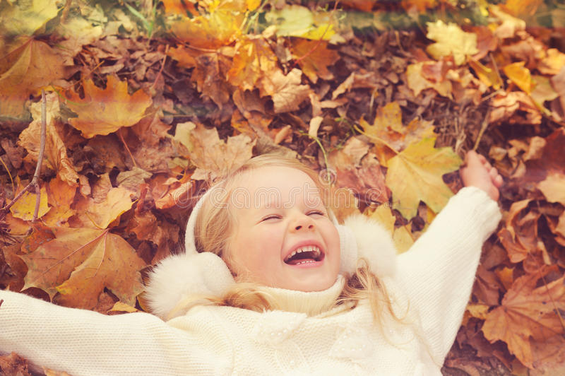 Little blonde girl portrait lying on autumn yellow maple leaves outstretched hands and smiling. stock images