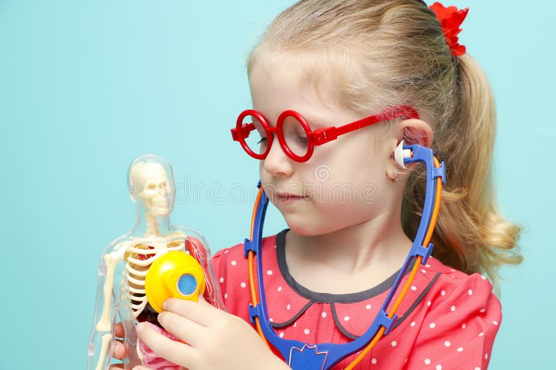 Little blonde girl with red glasses listen heart with stethoscope. Little funny blonde girl with red glasses listen heart with stethoscope. The skeleton of a stock images