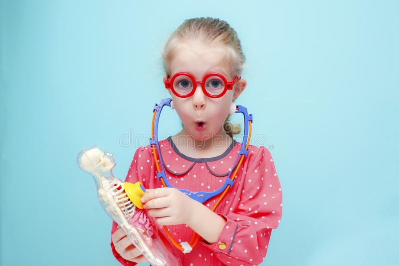 Little blonde girl with red glasses listen heart with stethoscope. Little funny blonde girl with red glasses listen heart with stethoscope. The skeleton of a royalty free stock images