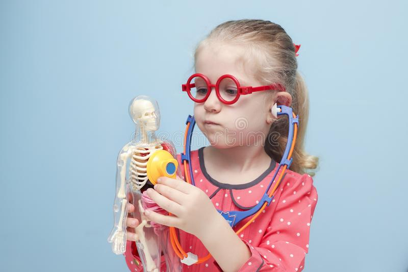Little blonde girl with red glasses listen heart with stethoscope. Little funny blonde girl with red glasses listen heart with stethoscope. The skeleton of a man stock photos