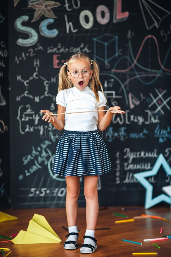 Little blonde girl with a surprised face with a ruler in her hands Pupil girl with big rulers against chalkboard with school stock images