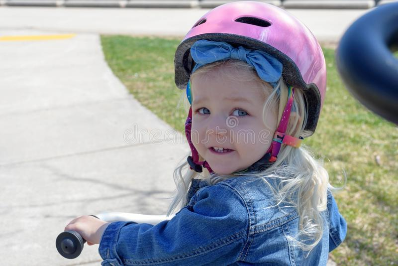 Little girl on trike looking over her shoulder stock images