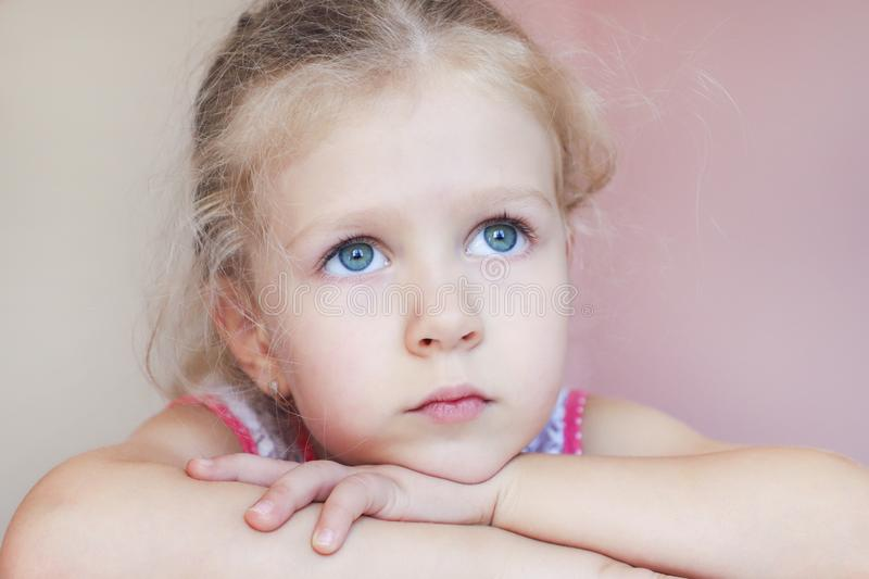 Little blonde hair girl with sad eyes looking up royalty free stock image