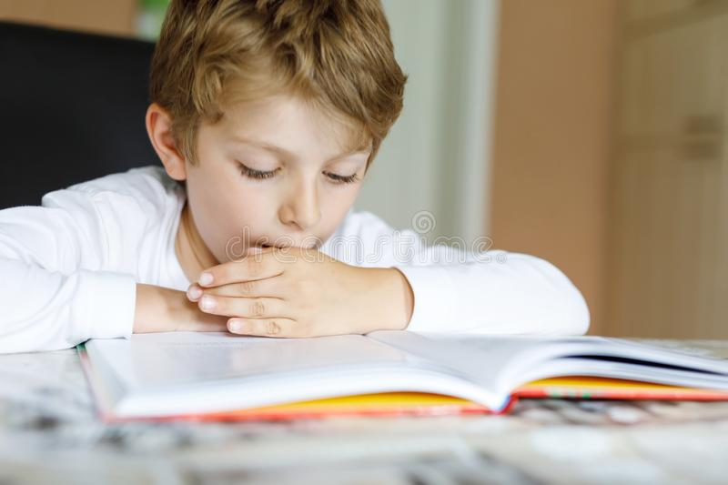 Little blonde school kid boy reading a book at home. Child interested in reading magazine for kids. Leisure for kids. Building skills and education concept stock images
