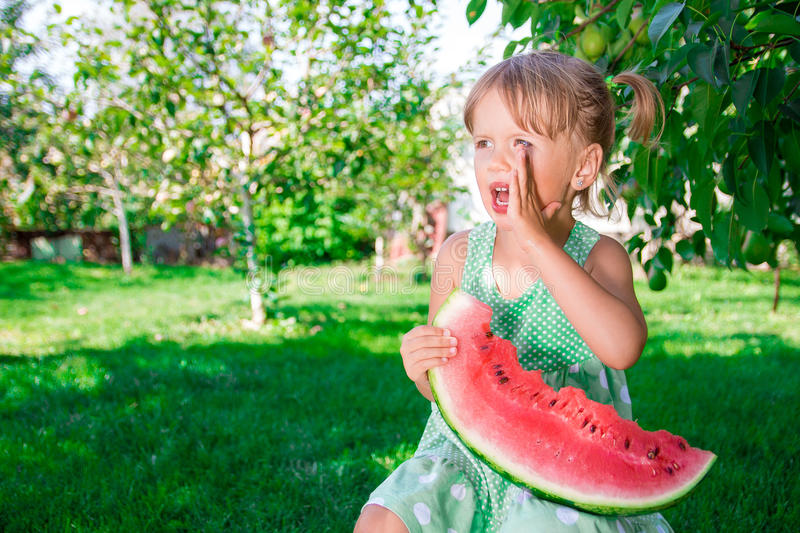 Little blonde with slice of watermelon in summer park. Happy. Screaming, calling royalty free stock photography