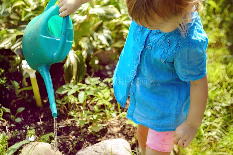 Little blonde in turquoise shirt watering flowers in the garden. stock photography