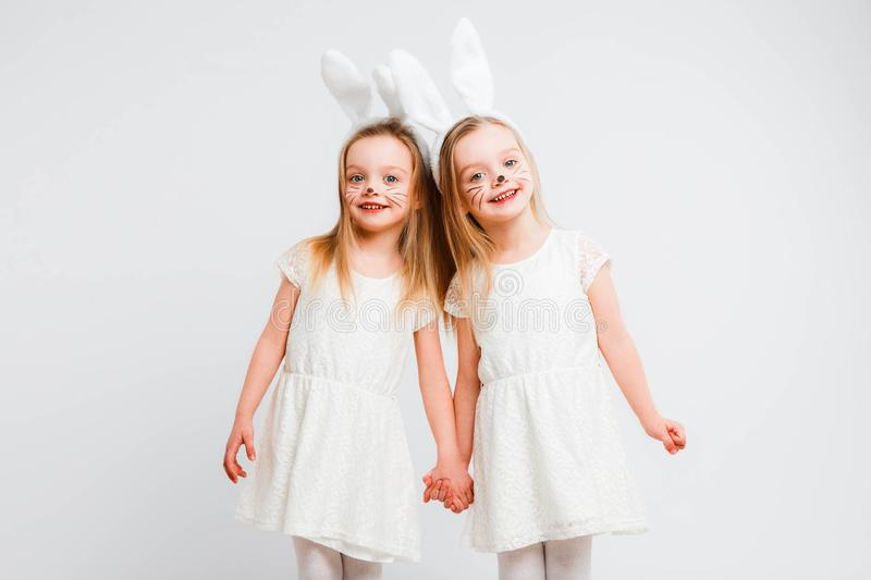 Little blonde twins in white dresses with rabbit ears. Studio photo on gray background. Kids celebrate Easter. stock photography