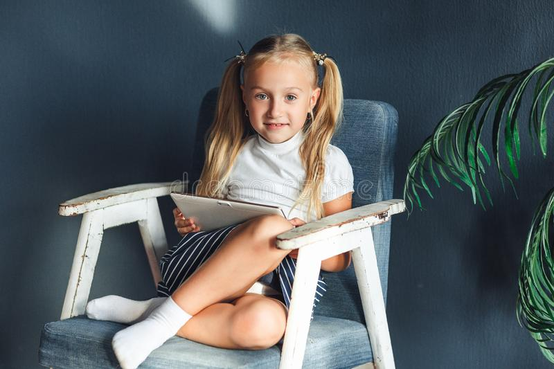 Little blondy girl sitting on a chair and doing homework for school, researching information on the tablet royalty free stock photo