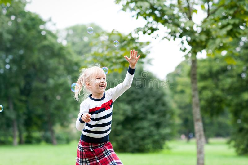 Little blondy girl playing with soap bubbles in summer park royalty free stock photography