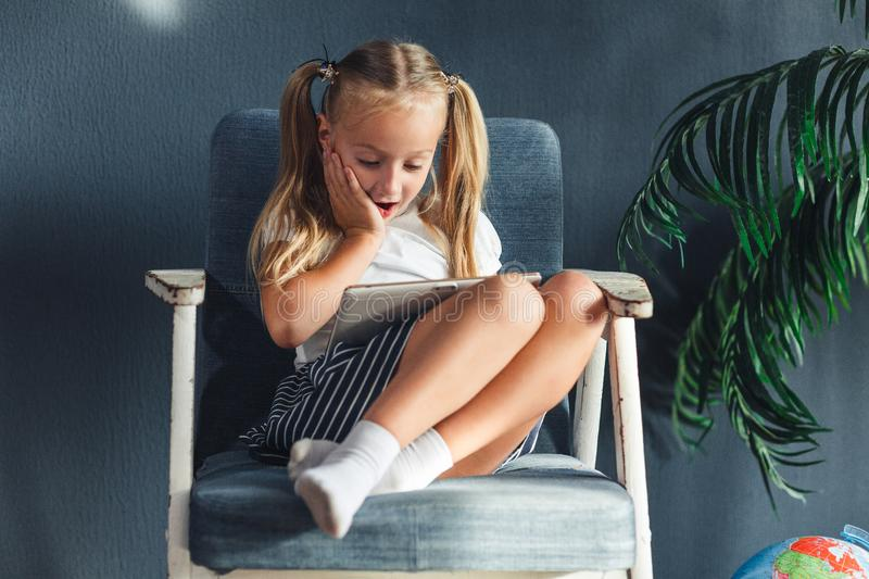 Little blondy girl sitting on a chair and doing homework for school, researching information on the tablet stock photo