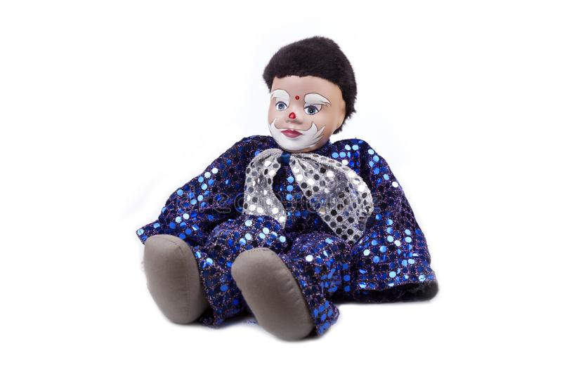 A little blue black haired boy clown like doll with shiny sequins and a bow on the neck, sitting pose. Isolated on white, detailed royalty free stock photo