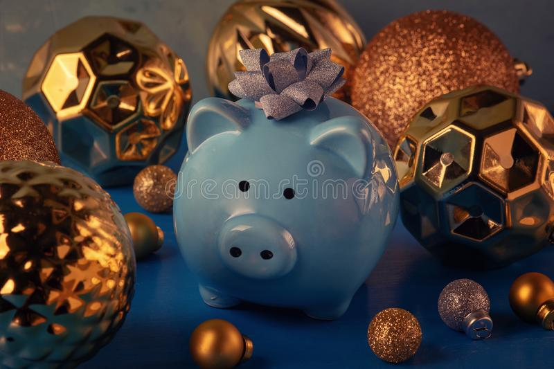 A little blue piggy bank with a silver bow on his head. Around big golden Christmas balls. Holiday card. A little blue piggy bank with a silver bow on his head stock photos