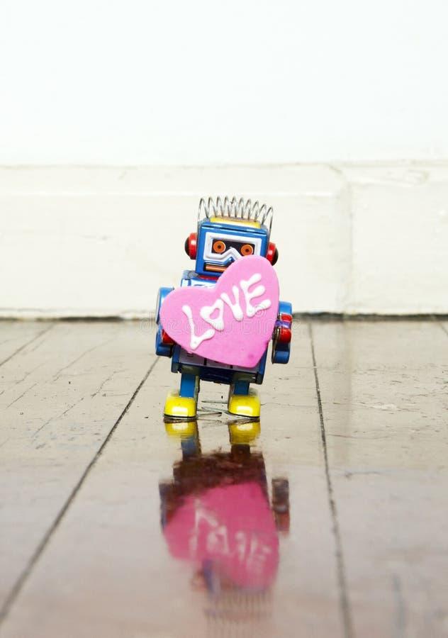 Little blue robot holding a big pink love heart stock photography