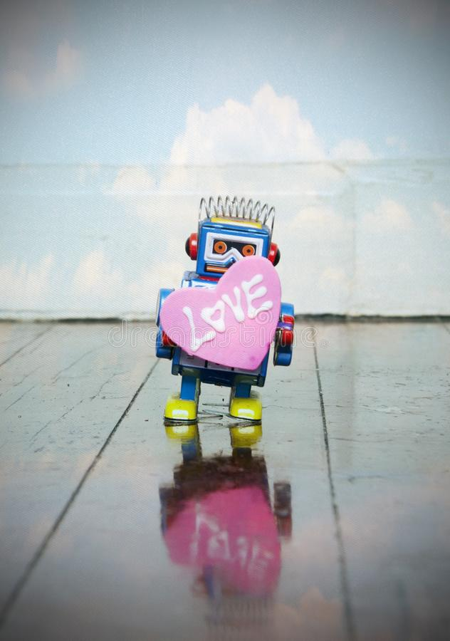 Little blue robot holding a big pink love heart royalty free stock photography