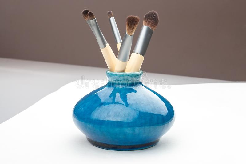 Little blue vase with makeup brushes stock image