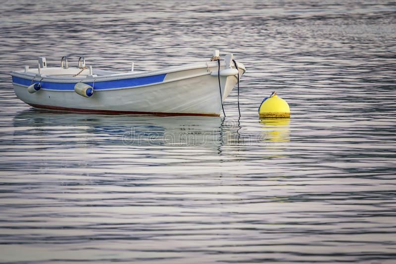 A little boat. Small colorful wooden fishing boat ,mooring to the buoy stock photography