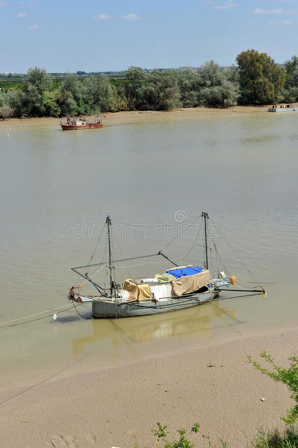 Little boats on the Guadalquivir River as it passes through Coria del Rio, Seville province, Andalusia, Spain. Fishing boats and barges on the River Guadalquivir royalty free stock image