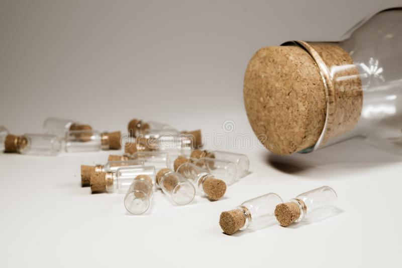 Empty little bottles with cork stopper isolated on white. big bottle with cork. transparent containers. Little bottles with cork stopper isolated on white. big stock images