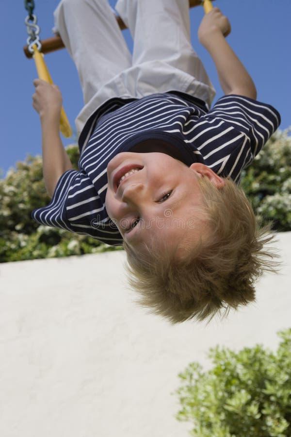 Little Boy à l'envers sur une oscillation photos stock