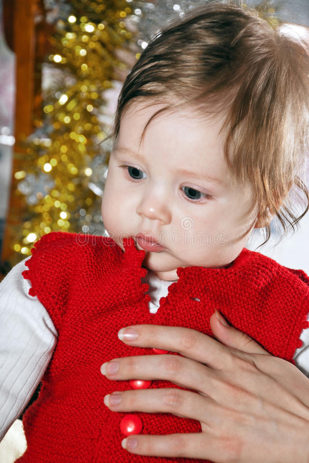 Little boy. Cute little kid in the red vest in the hands of parents royalty free stock photo