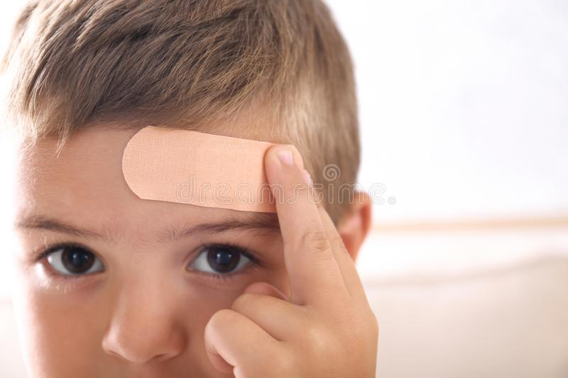 Little boy with adhesive bandage on  indoors, closeup. Little boy with adhesive bandage on forehead indoors, closeup royalty free stock images