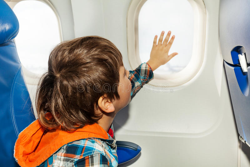 Little boy on airplane touch window with hand. Boy sit in commercial plane touching window with hand royalty free stock photography