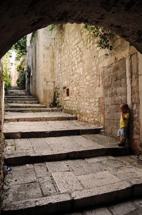 Little boy alone. Alone little boy standing against stone wall, Korcula old town, Croatia