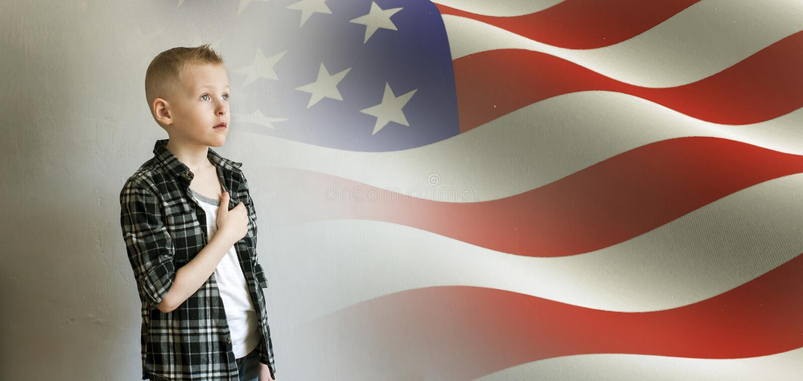 Little boy and American flag. Proud boy paying tribute to American flag royalty free stock photography