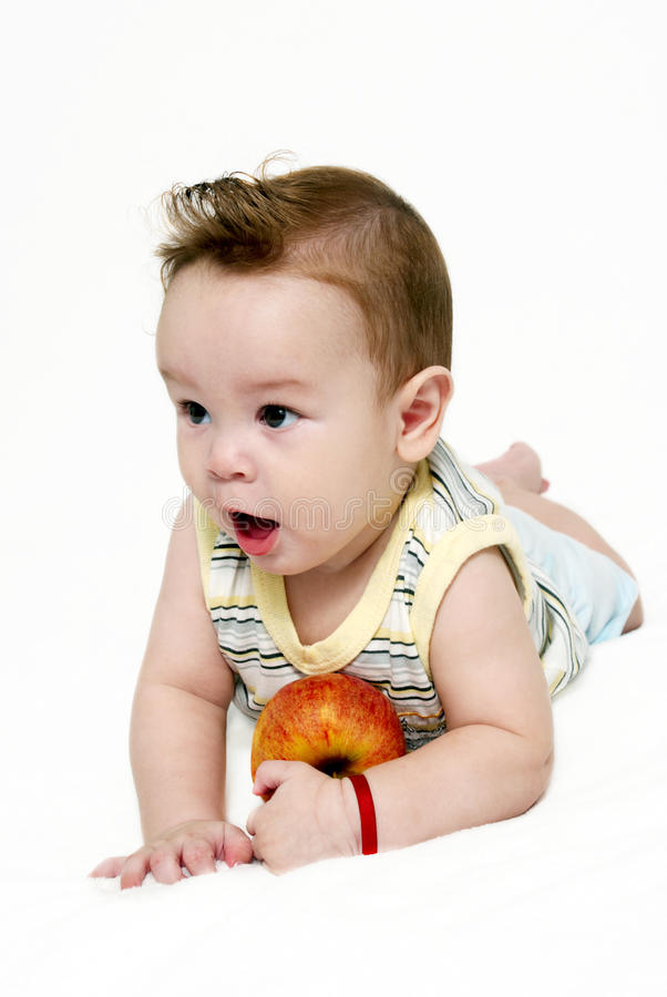 Little boy with an apple on a light background. Portrait of the little boy with an apple on a light background stock images