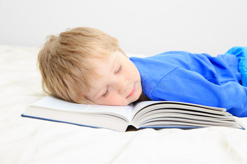 Little boy asleep on open book. Education concept stock photo