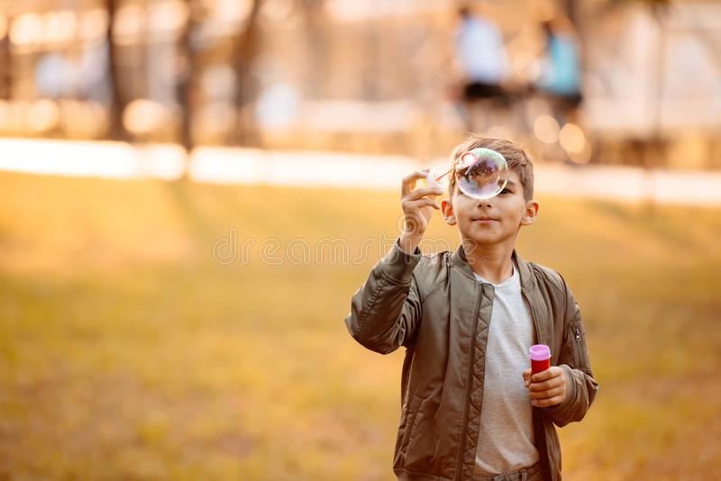 Little boy in an autumn jacket playing with soap bubbles royalty free stock photos