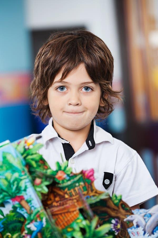 Little Boy avec le métier dans le jardin d'enfants images libres de droits