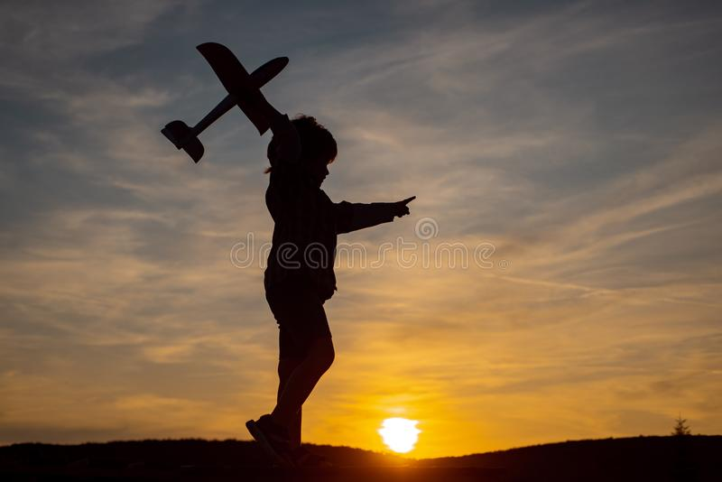 Little boy aviator over sunset sky. Boy dreams of becoming a pilot. Cute child walking in the wheat golden field on a stock photo