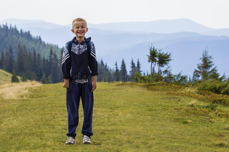 Little boy with a backpack hiking in scenic summer green Carpathian mountains. Child standing alone enjoying landscape mountain vi royalty free stock images